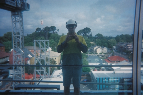 Author reflected in window of work site